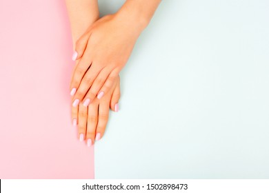 Stylish fashionable female manicure with a plain color. Hands of a beautiful young woman on a pink and blue background.