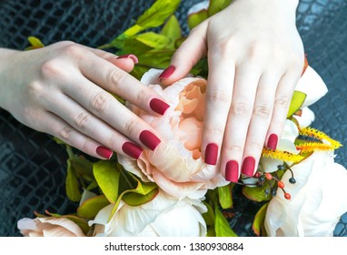 Stylish fashionable female red matte manicure, square shape, on a black background, crocodile skin with artificial peony flower