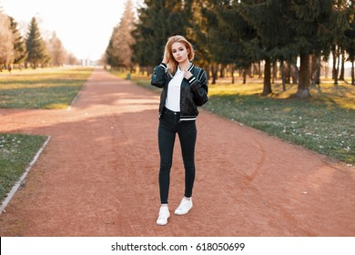 Stylish fashionable girl in a jacket, jeans and white shoes is standing in the park at sunset