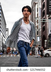 Stylish Fashionable Man Walking on a City Street. Asian Male Model Wearing casual clothes, white t-shirt, jeans, button shirt posing posing walking in the City.