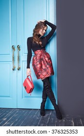 Stylish fashionable outfit slim beautiful girl figure diet, catalog collection of clothing, attractive, sexy woman wearing red skirt classic fitting black sweater, leather small handbag room blue door
