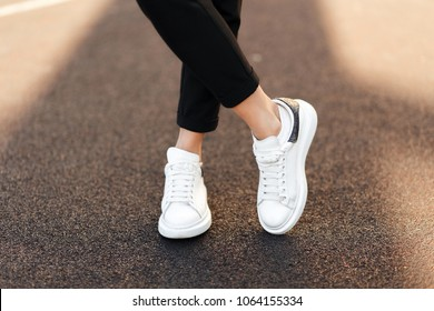 Stylish fashionable white women's leather shoes on asphalt on a sunny day. Female legs with sneakers