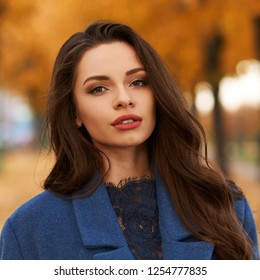 Stylish fashionable woman in blue coat and white boots standing in autumn colorful park. Elegant lady with white handbag