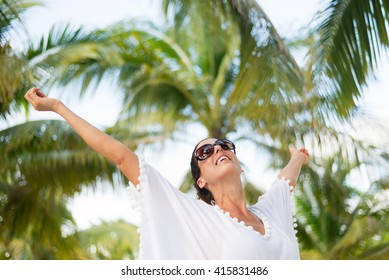 Stylish fashionable woman having fun and enjoying relaxing summer tropical vacation at beach. Female brunette wearing fashion white kaftan and sunglasses raising arms.