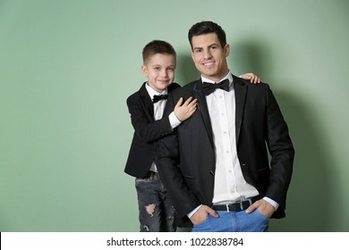 Stylish father and son in jackets on color background