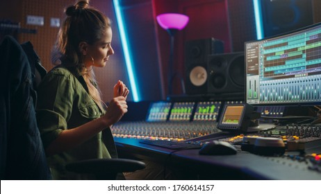 Stylish Female Audio Engineer Working in Music Recording Studio, Uses Mixing Board, Software to Create Modern Sound. Creative Girl Artist Musician Working on Control Desk to Produce New Song.