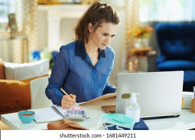 stylish female in blue blouse in the modern living room in sunny day working in temporary home office during the coronavirus epidemic.