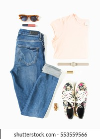 Stylish female clothes set. Woman/girl outfit on white background. Blue jeans, peach t-shirt, flower print sneakers, hand watch, retro sunglasses. Flat lay, top view