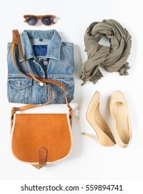 Stylish female clothes set. Woman/girl outfit on white background. Blue denim jacket, gray scarf, vintage cross bag, cream shoes and retro sunglasses. Flat lay, top view.