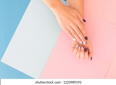 Stylish female pink and blue manicure. Beautiful young woman's hands on pink pastel background with festive multicolored confetti. Trendy geometric pattern.