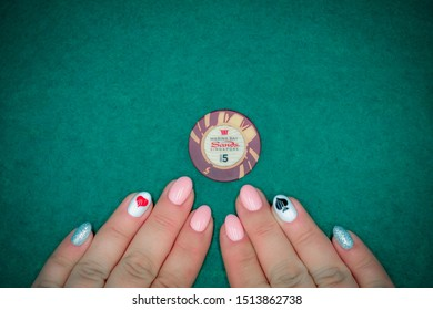 Stylish female poker manicure and chip from casino Marina Bay Sands Singapore on a green background. Life is a game. Singapore - February 25, 2016.