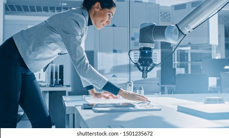 Stylish Female Robotics Engineer Leans on the Table Works with Blueprints, Documents and Tablet Computer, She's Programming Robot Arm Movements