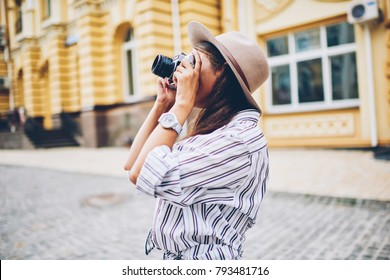 Stylish female traveler spending holiday trip on hobby taking photos of urban settings standing on street.Professional photographer using vintage cameras for making picture of city architecture