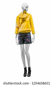Stylish female yellow turtleneck and black shorts with embroidered colorful flowers on mannequin. Female autumn outfit