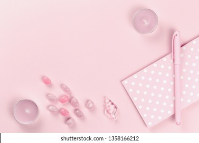 Stylish feminine accessories, ornaments, gifts, sweets and purse items in blue pastel colors on rose pink background and polka dot. Copy space, mock up. Women's day or bloggers concept. Flat lay