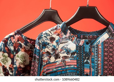 Stylish feminine clothes hanging on red background, closeup shot
