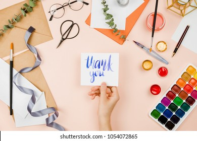 "Stylish flatlay with art supplies, envelopes, brushes, watercolors, glasses, pen and woman's hand holding a handmade card with handlettered inscription ""Thank you"". Pastel background"