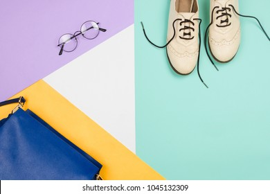 Stylish flatlay with female fashion accessories and clothes: shoes, bag and glasses, blue, violet, white and yellow background. Copyspace