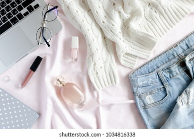 Stylish flatlay of laptop, glasses, silver notepad, women cosmetics, clothes, accessories