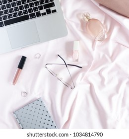 Stylish flatlay of laptop silver notepad, and women cosmetics, accessories