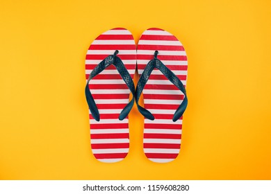 Stylish flip flop sandals with USA flag pattern, top view with copy space over yellow background