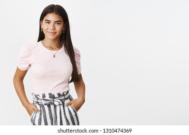 Stylish friendly-looking confident young charming teenage indian girl in striped pants and t-shirt holding hands in pockets and smiling delighted at camera as feeling assertive and carefree