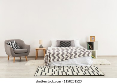 Stylish furniture with big bed near light wall