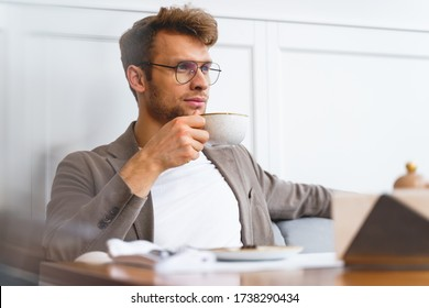 Stylish gentleman in glasses holding cup of hot drink and looking away while sitting at the table in cafeteria