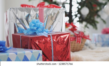 Stylish gift boxes and decorated blurred fir tree on the background