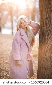 Stylish girl 20-24 year old wearing fluffy winter coat posing in park over nature background. Looking at camera. Autumn season.