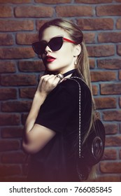 Stylish girl in black dress and sunglasses posing by the brick wall. Modern youth fashion.