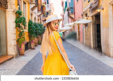 stylish girl with boater with tape and sunglasses walking on the street of the city. She is smiling