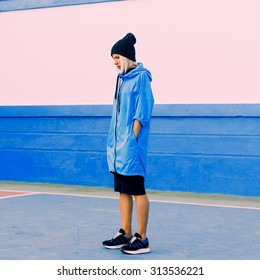 Stylish Girl in bright blue coat in blue location Blue color in trend