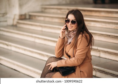 Stylish girl in a brown coat and a scarf with glasses. Using a phone in paris france. Makeup