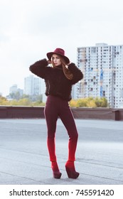 Stylish girl in burgundy hat and autumn outfit posing on a building roof