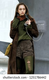 Stylish girl calls on city phone. She is dressed in a boho style: brown coat, yellow bag, green sweater.