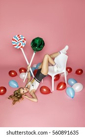 Stylish girl with candies and balloons on pink background