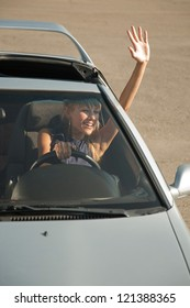 Stylish girl in  car is waving her hand