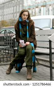 Stylish girl eating cakes while sitting on a bench against the background of the historic part of the city. She is dressed in a boho style: a green jumpsuit and a long blue scarf.
