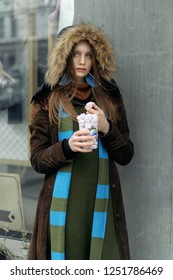 Stylish girl eating cakes while standing at the window of a vintage shop. She is dressed in a boho style: a green jumpsuit, a fur hood, and a long blue scarf.