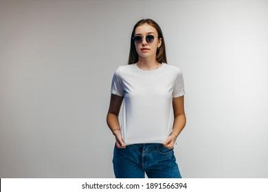Stylish girl in glasses wearing white t-shirt posing in studio