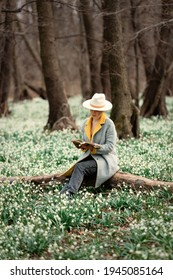 stylish girl in gray coat with a book in snowdrops meadow in forest