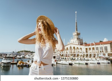 Stylish girl in a hat unrecognizable, stands against the backdrop of the Maritime Station in Sochi