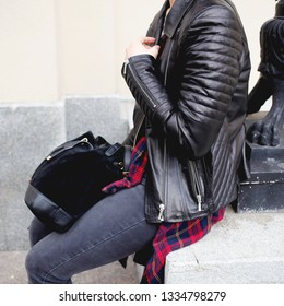 stylish girl with leather bag and black jacket walking through the city on a warm sunny day