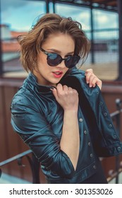 Stylish girl in the leather jacket and sunglasses outdoor