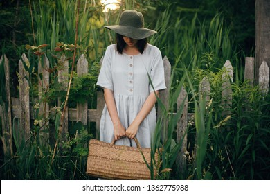 Stylish girl in linen dress holding rustic straw basket at wooden fence among green cane. Boho woman in hat relaxing and posing in summer countryside in evening. Atmospheric rural moment