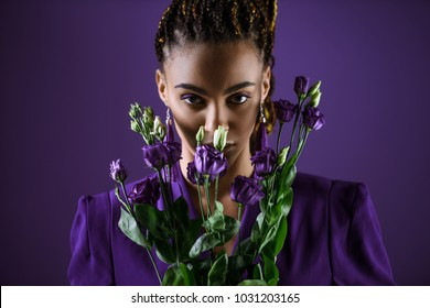 Stylish  girl posing with purple eustoma flowers, isolated on purple, ultra violet trend