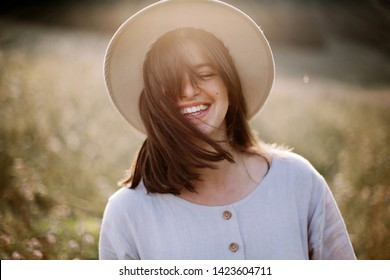 Stylish girl in rustic dress smiling and waving hair in sunny meadow in mountains. Portrait of happy boho woman in countryside at sunset, positive vibes, rural simple life. Atmospheric image