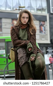 Stylish girl shows clothes on the background of the flow of cars. She is dressed in a boho style: brown coat, yellow bag, green sweater, shorts and torn stockings