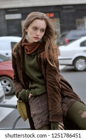 Stylish girl shows clothes on the background of the flow of cars. She is dressed in a boho style: brown coat, green sweater, shorts and torn stockings